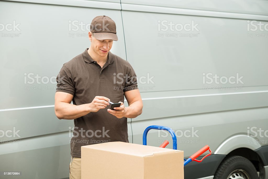 Delivery Man Checking List On Mobile Phone stock photo