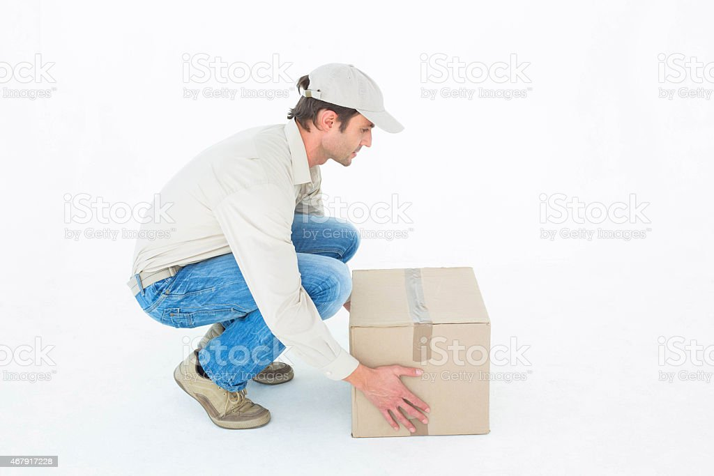 Delivery man crouching while picking cardboard box stock photo