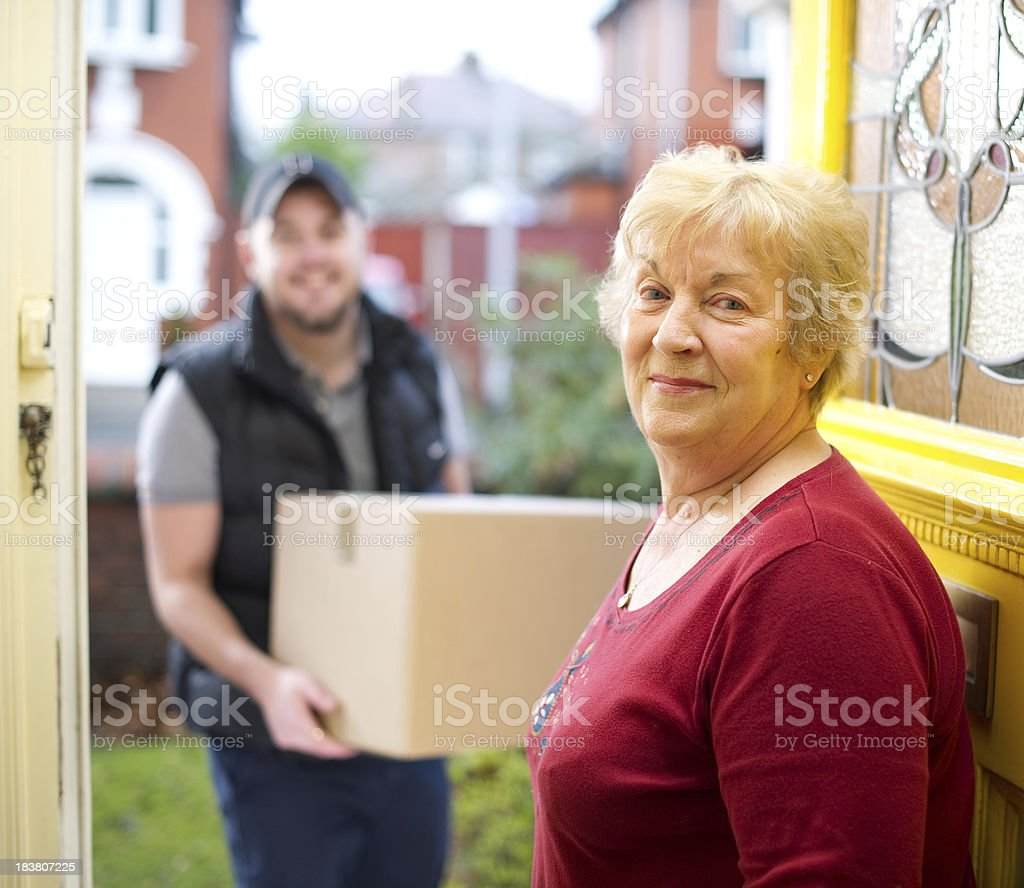Delivery man delivering gran her parcels royalty-free stock photo