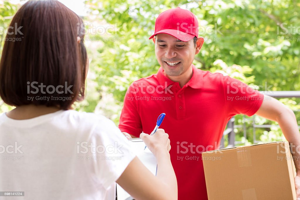 Delivery man delivering parcel to a woman stock photo