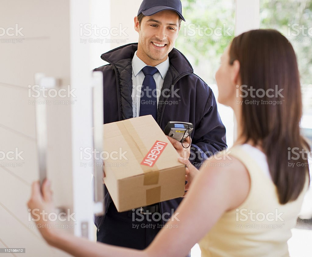 Delivery man handing box to woman stock photo