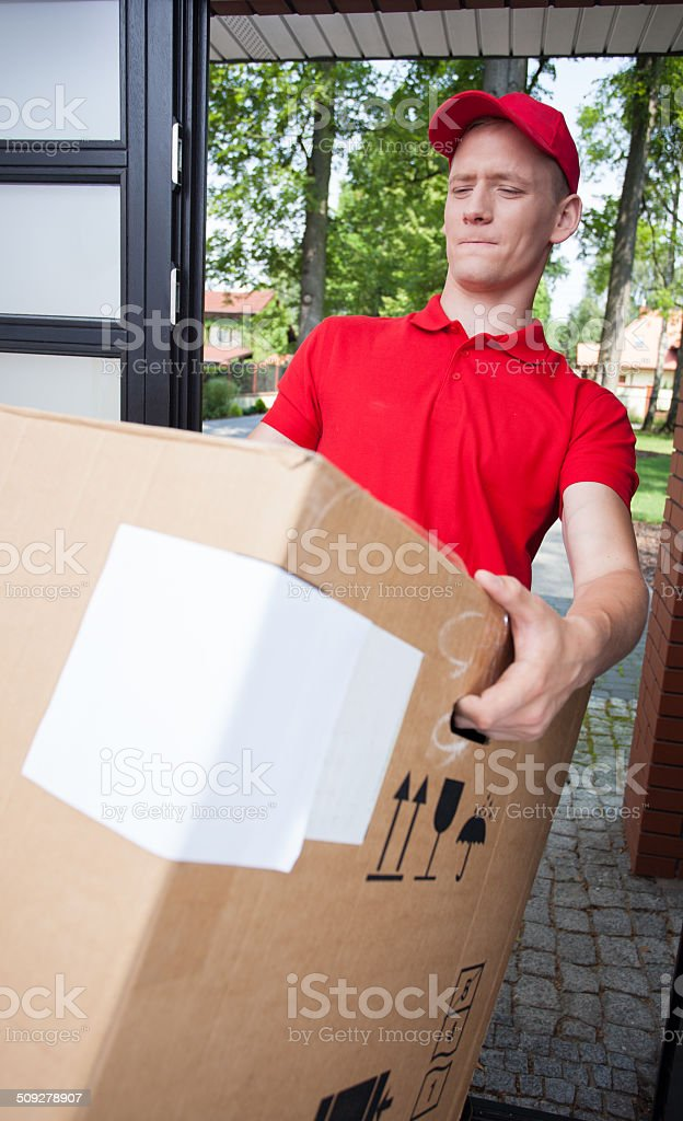 Delivery man holding a heavy box stock photo