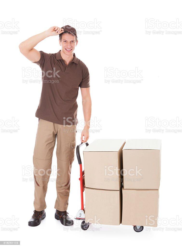 Hombre parado cerca de entrega y cajas carretilla industrial - foto de stock