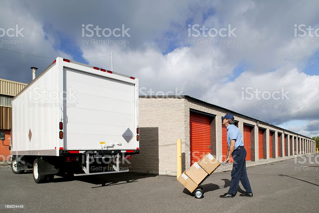 Delivery man taking boxes to the truck on a dolly stock photo