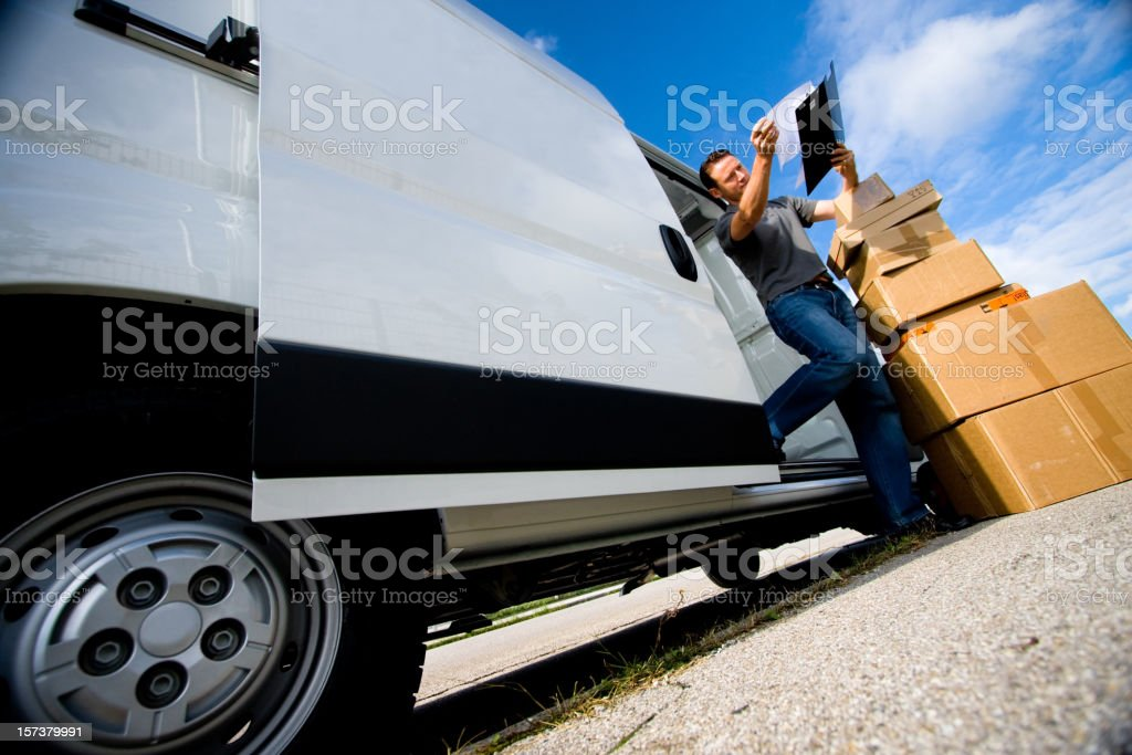 Delivery man unloading boxes from truck stock photo