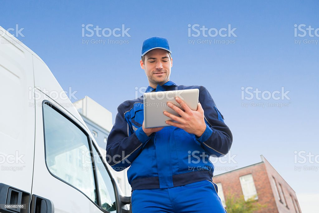Delivery Man Using Digital Tablet By Truck Against Sky stock photo