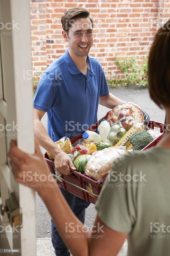 Delivery man with box full of online grocery shopping order royalty-free stock photo