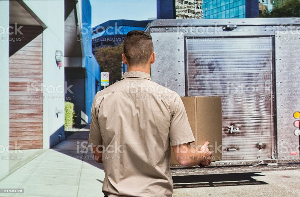 Delivery man with cardboard box stock photo