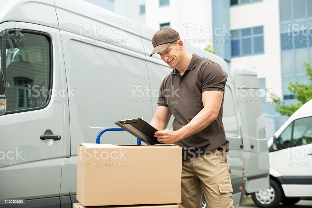 Delivery Man Writing On Clipboard stock photo