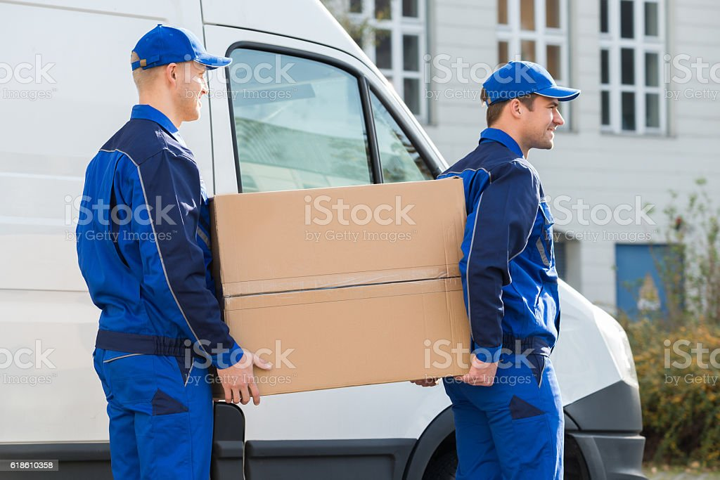Delivery Men Carrying Cardboard Box By Truck stock photo