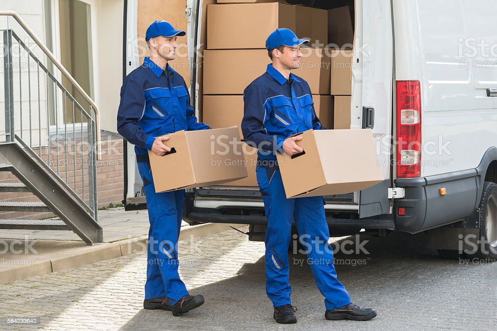 Delivery Men Carrying Cardboard Boxes stock photo