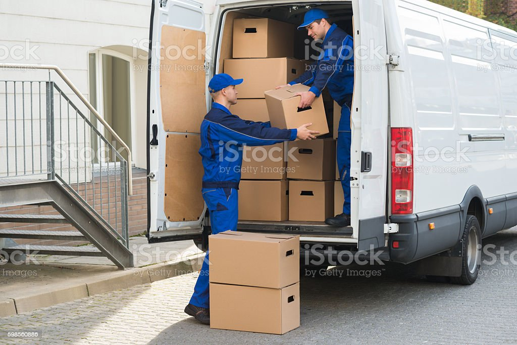 Delivery Men Unloading Boxes From Truck stock photo