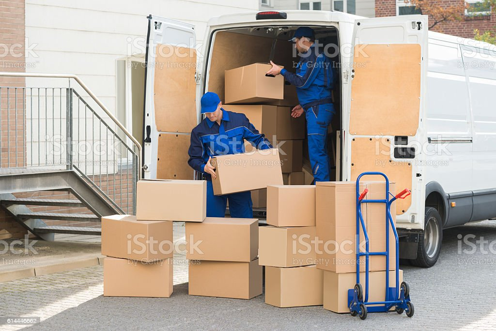 Delivery Men Unloading Boxes On Street stock photo