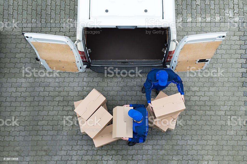Delivery Men Unloading Cardboard Boxes From Truck On Street stock photo