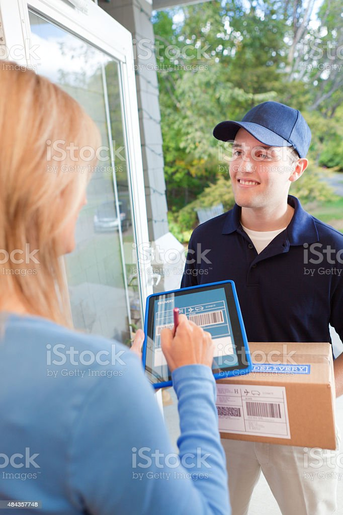A young Caucasian delivery man in the process of delivering mail...