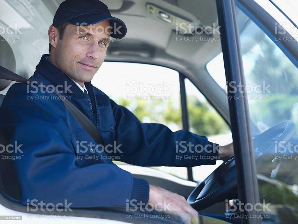 Delivery person driving van stock photo