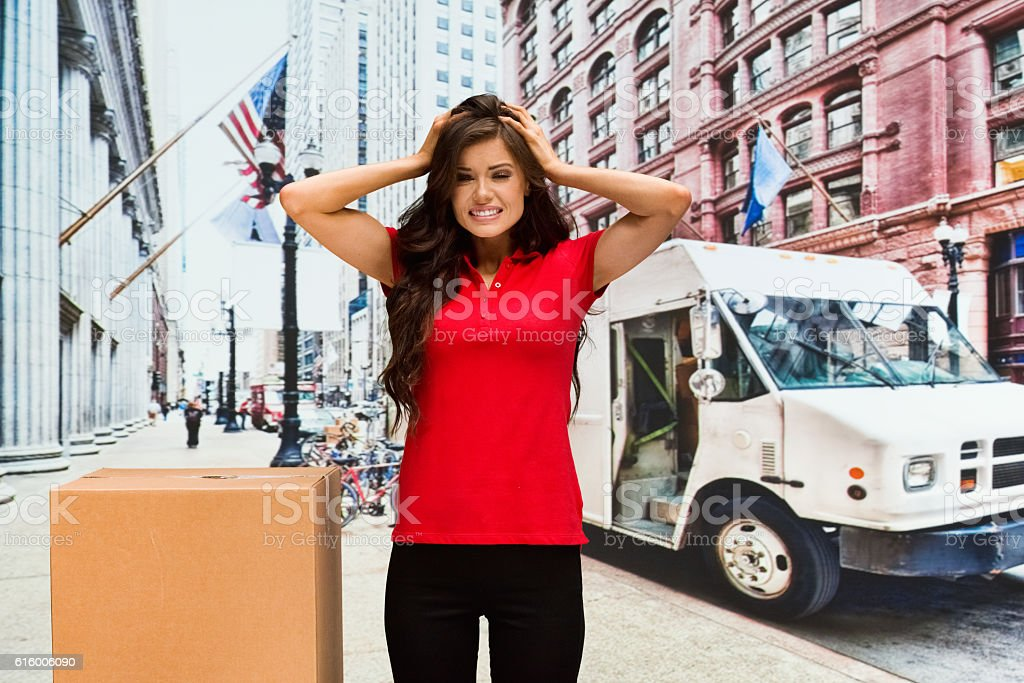Delivery person looking frustrated outdoors stock photo