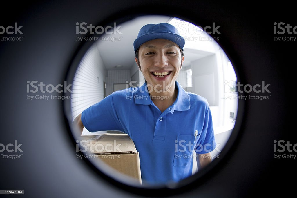 Delivery person seen through peep window stock photo