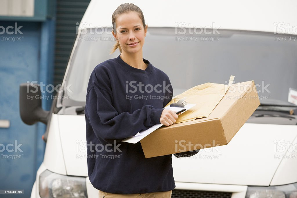 Delivery person standing with van, clipboard and box royalty-free stock photo
