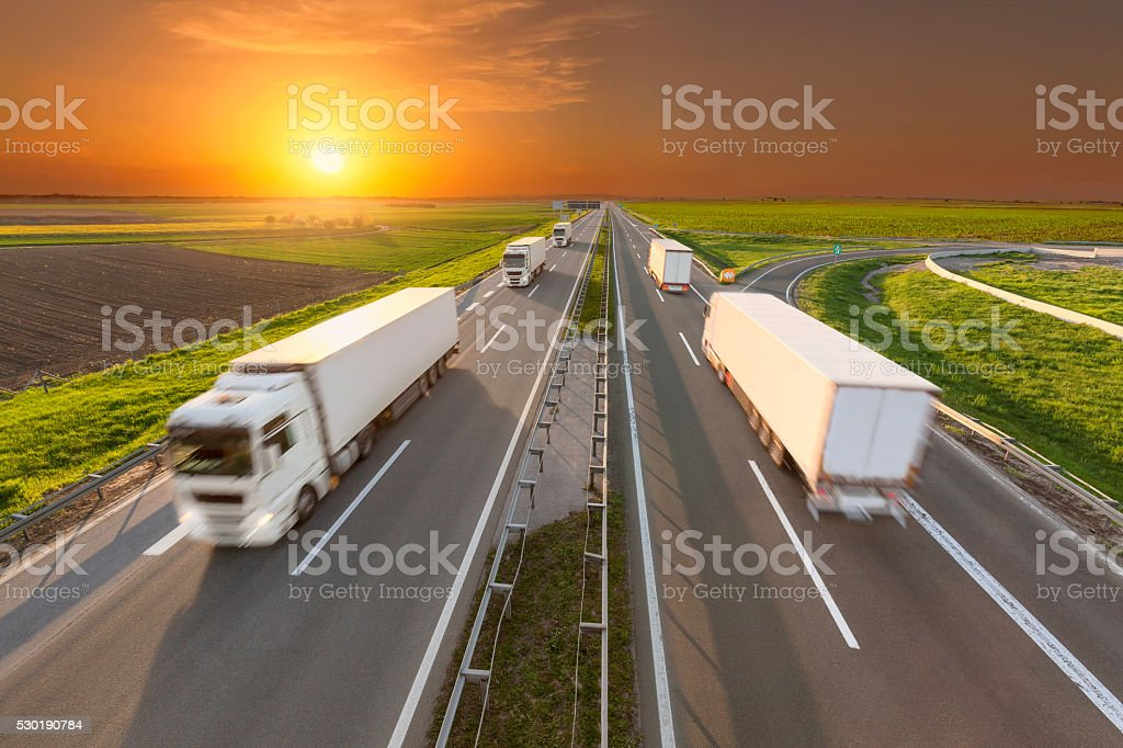 Delivery reefer transport trucks on the empty highway at sunset stock photo