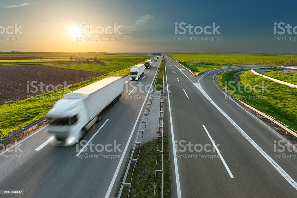 Delivery transport trucks on the highway at idyllic morning stock photo