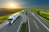 Delivery transport trucks on the highway at idyllic morning