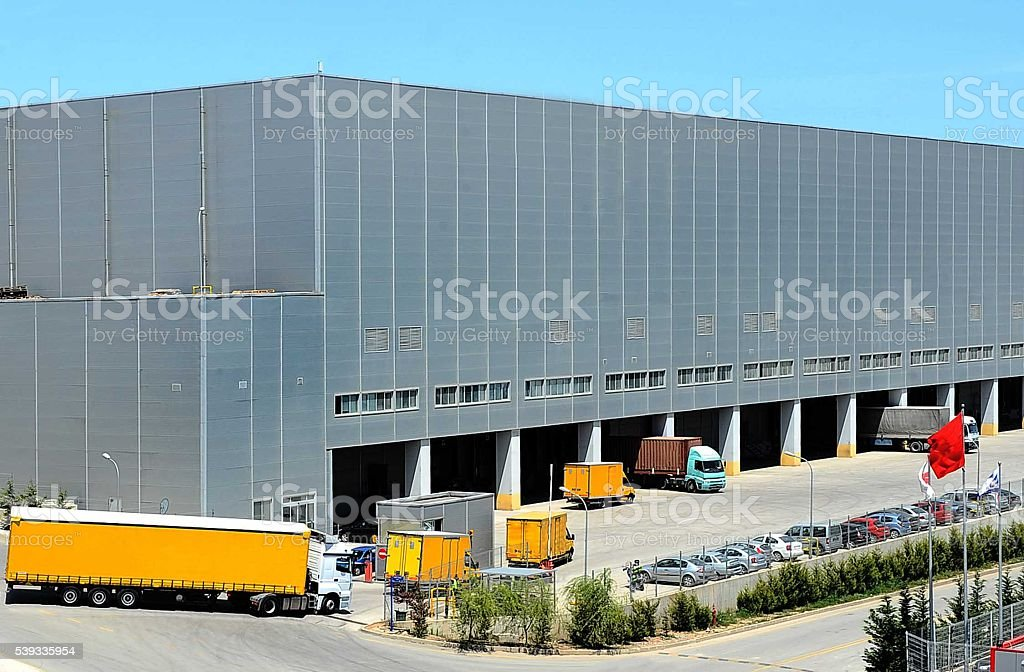 Delivery trucks entering warehouse parking stock photo