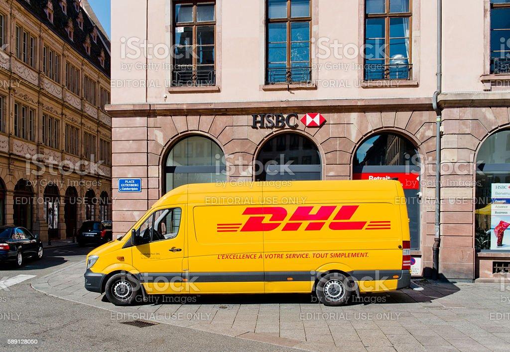 DHL delivery van leaving after distributing parcels stock photo