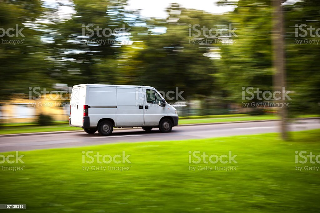 Delivery van moves on road stock photo