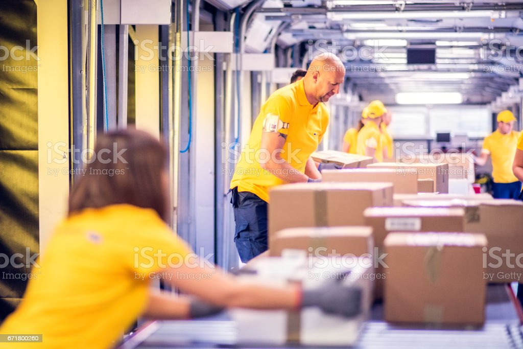 Delivery warehouse workers handling packages on conveyor belt stock photo