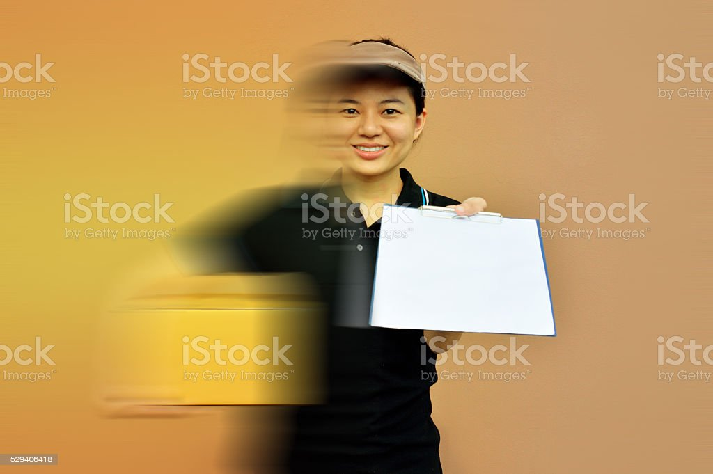 Delivery woman in a rush delivering service with cardboard boxes stock photo