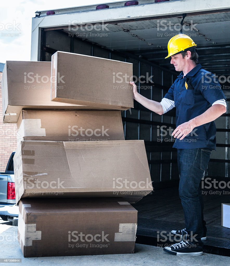 Delivery Worker Loading Damaged Boxes on Hand Truck stock photo