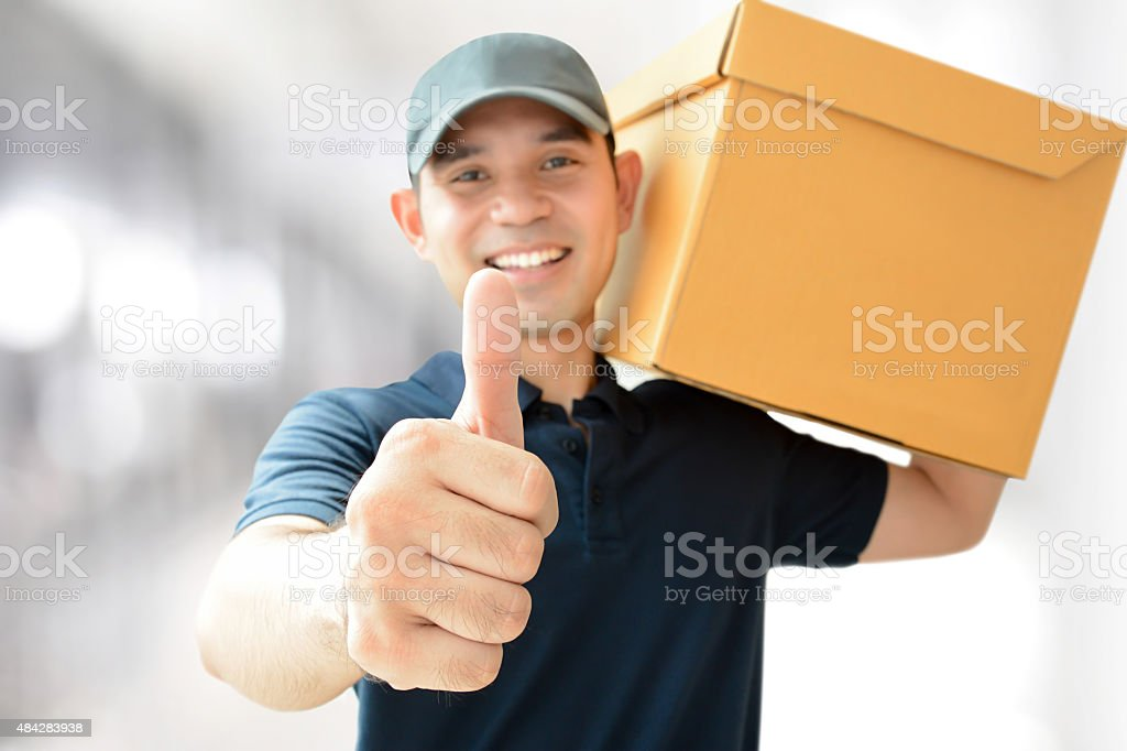 Deliveryman carrying a parcel box giving thumbs up stock photo