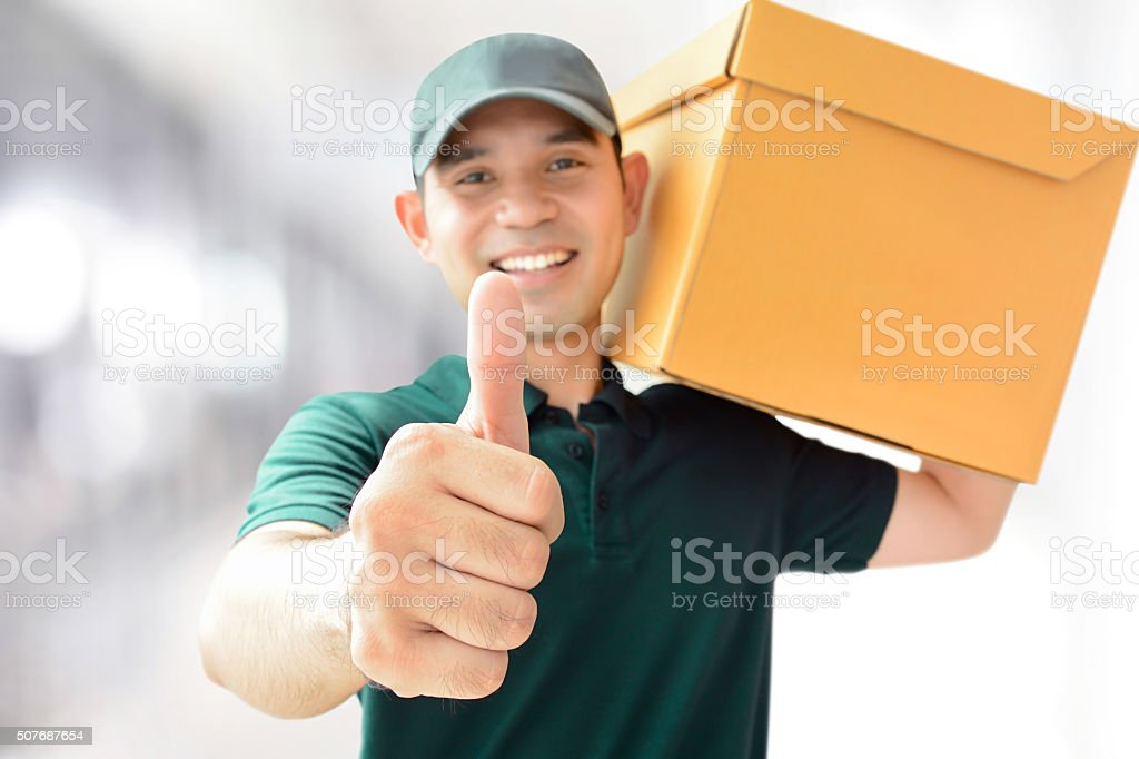 Deliveryman carrying a parcel box, giving thumbs up stock photo