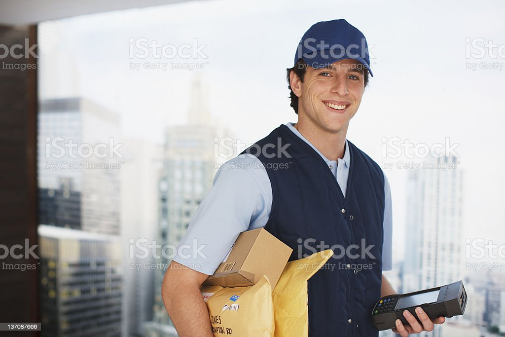 Deliveryman carrying packages and electronic device stock photo