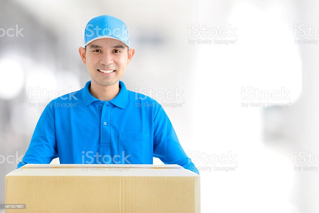 Deliveryman giving a cardboard parcel box stock photo