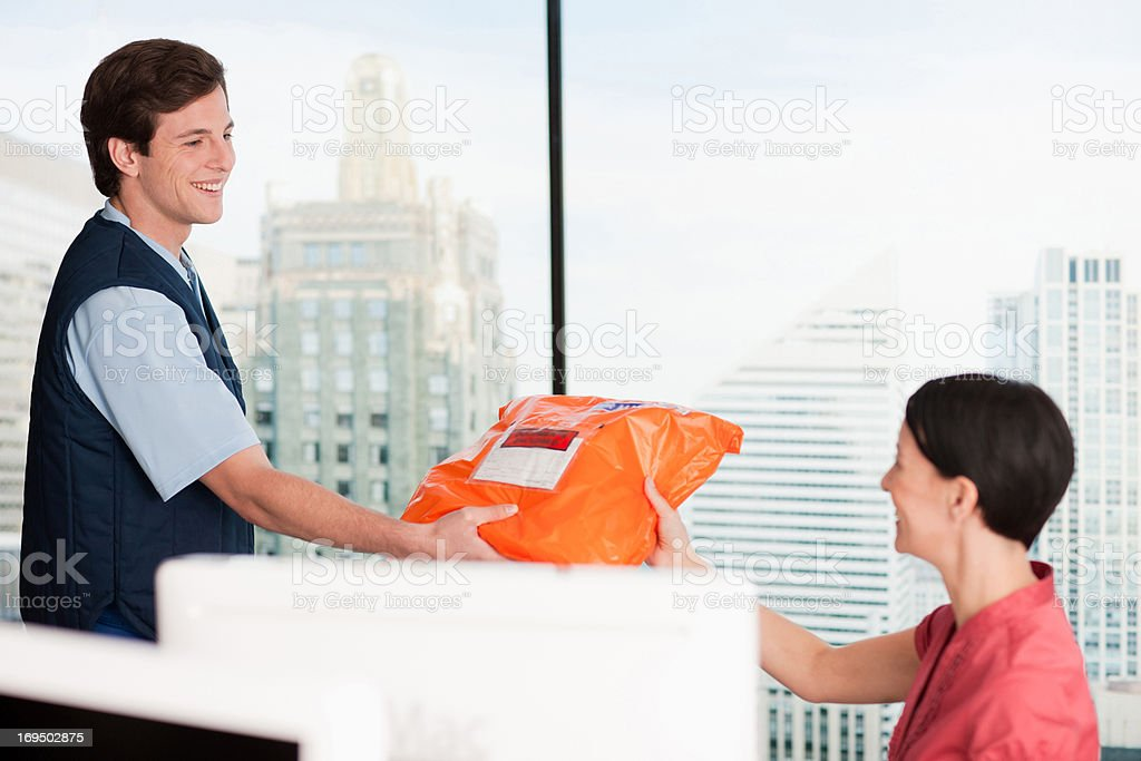 Deliveryman handing package to businesswoman stock photo