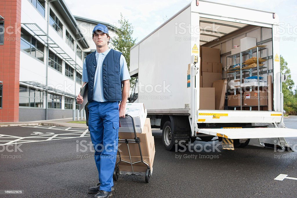 Deliveryman puling boxes on hand truck stock photo