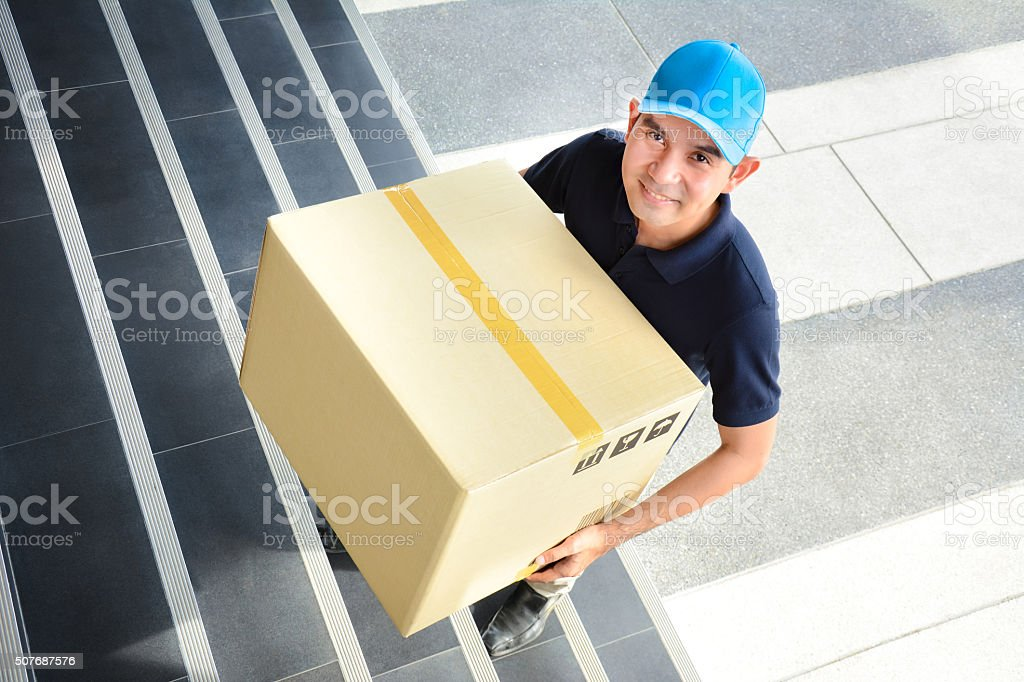 Deliveryman walking up stairs, carrying a big parcel box stock photo