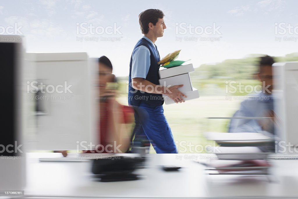 Deliveryman walking with packages in office stock photo