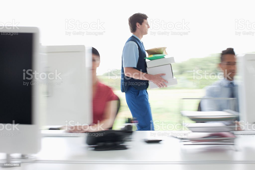 Deliveryman walking with packages in office royalty-free stock photo