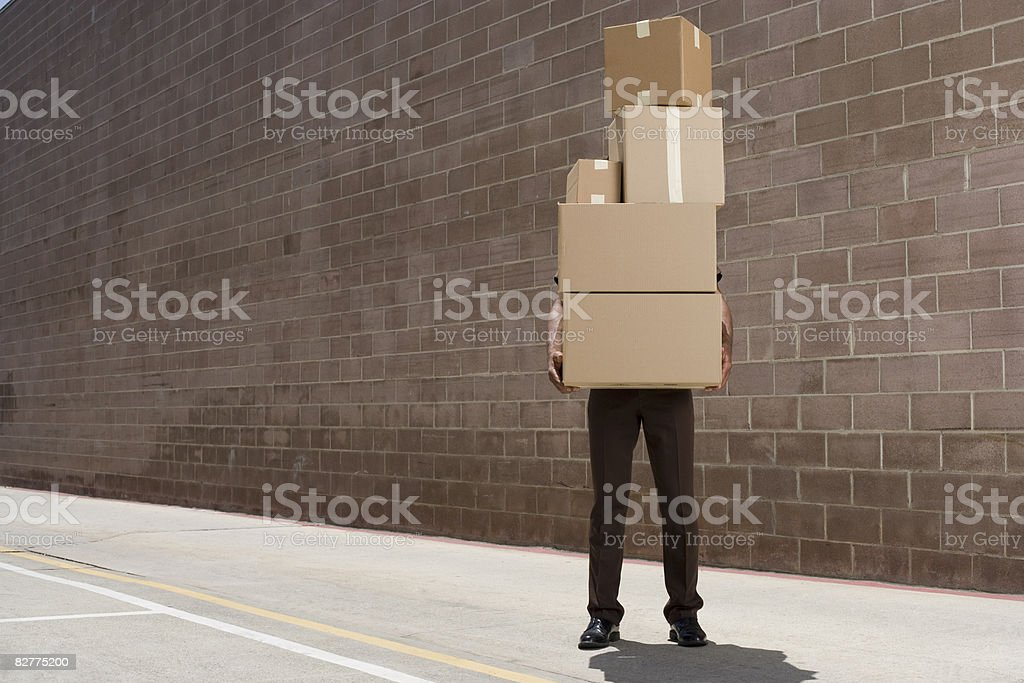 delivery-person carrying boxes stock photo