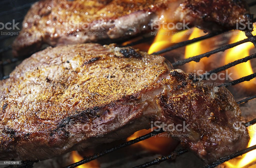 Delmonico Steaks Grilling on a Fire royalty-free stock photo