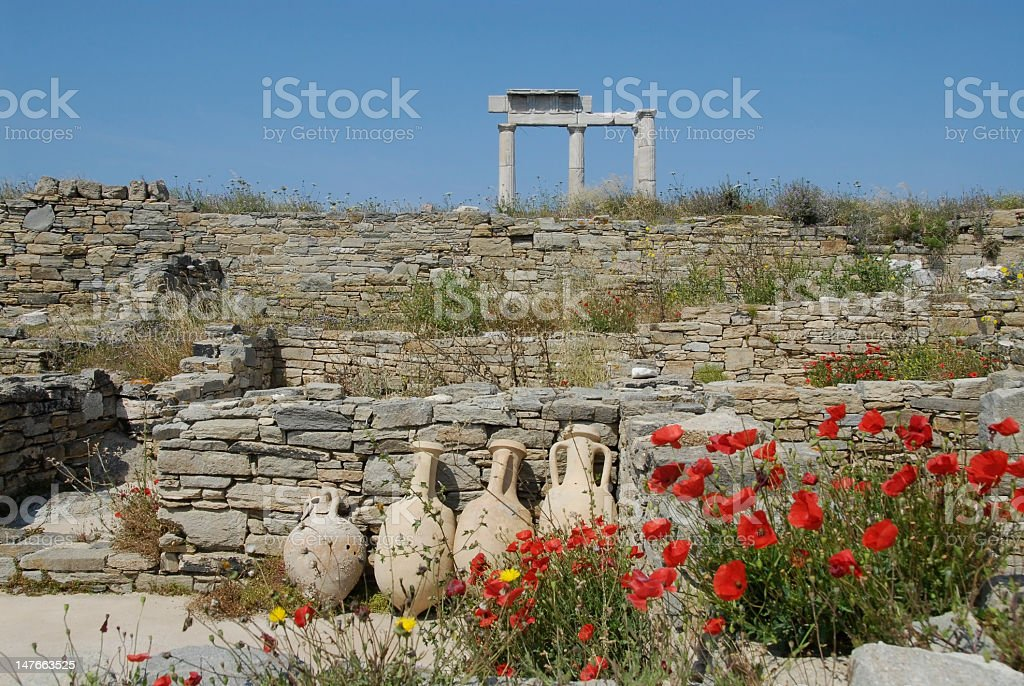 Delos, Greece. Old ruins with earthenware urns, columns and poppies. stock photo