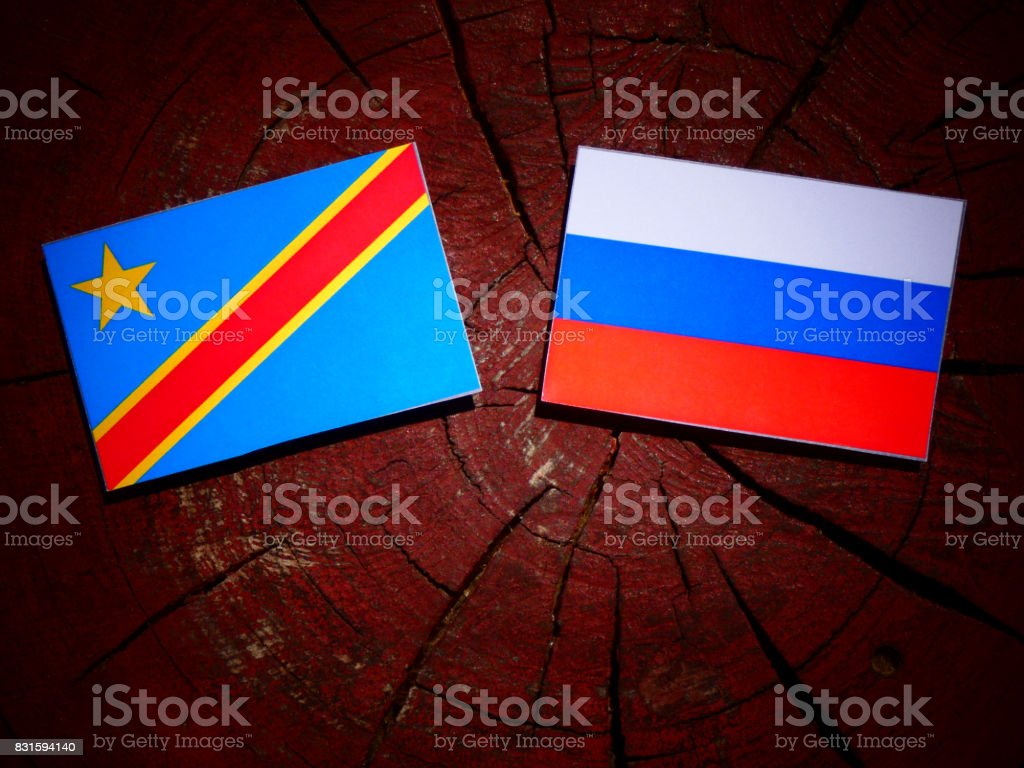 Democratic Republic of the Congo flag with Russian flag on a tree stump isolated stock photo