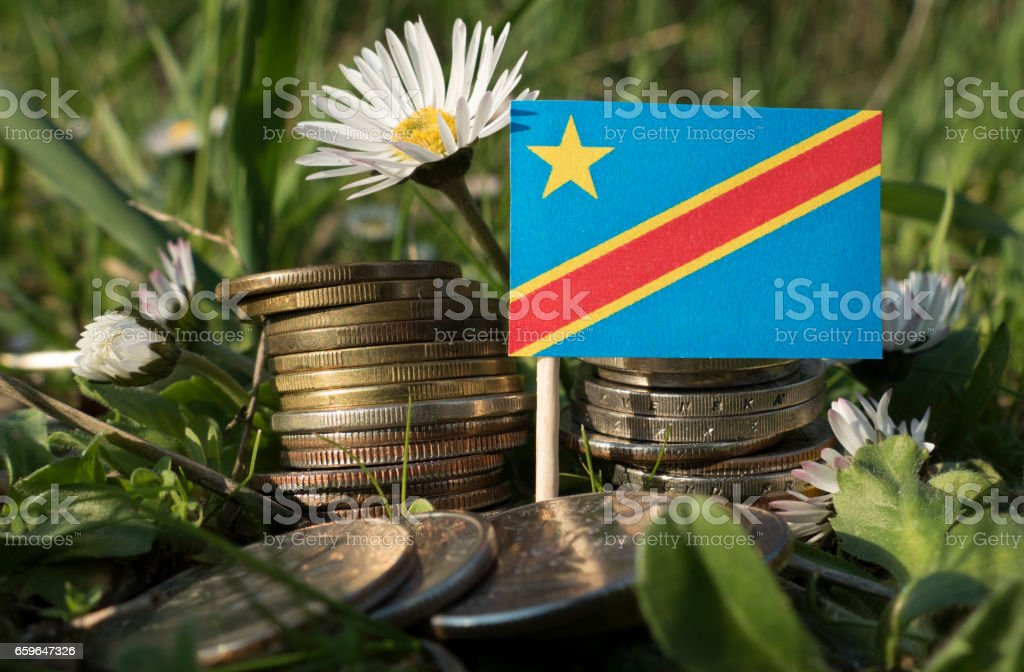 Democratic Republic of the Congo flag with stack of money coins with grass and flowers stock photo