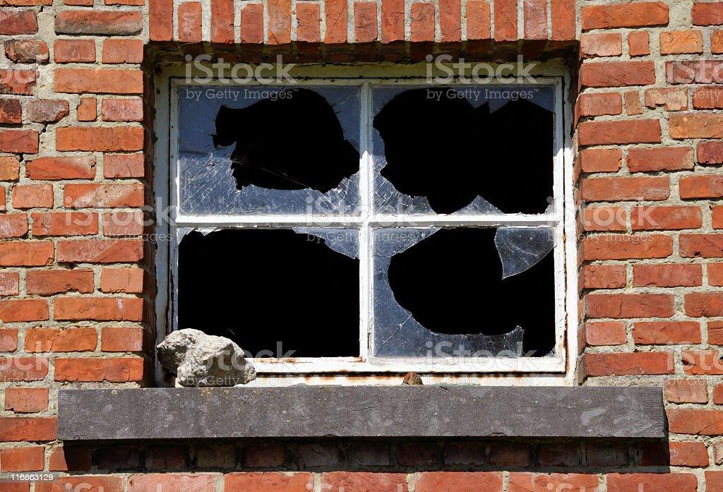 Demolished window with broken glass and stone stock photo