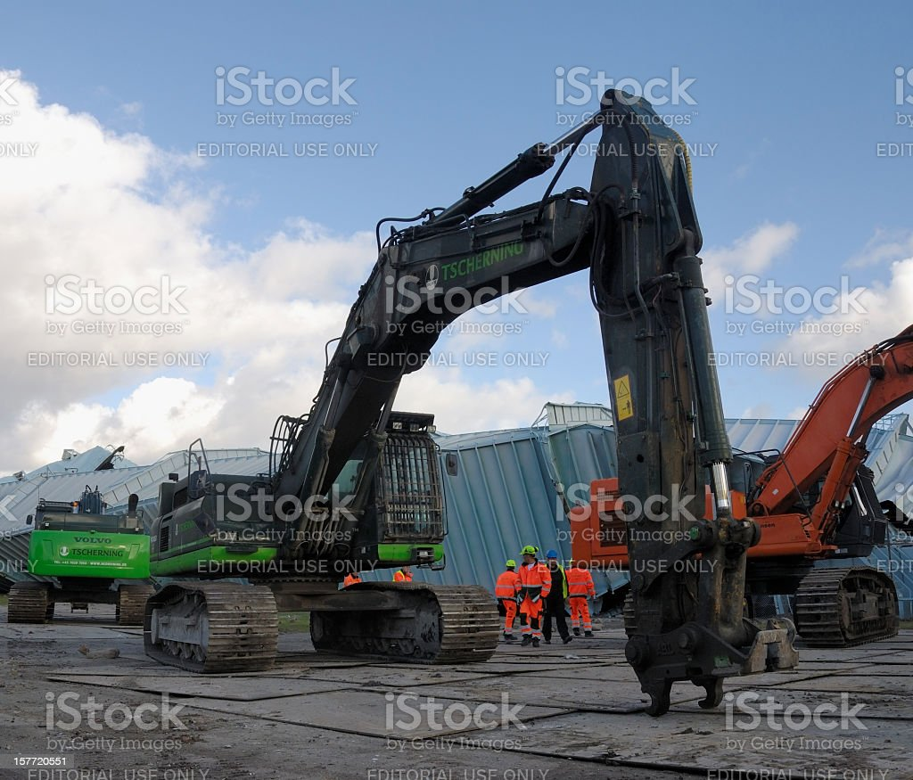 Demolition excavators and workers in front of exploded gas tower royalty-free stock photo