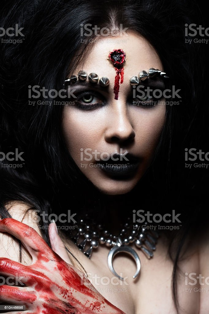 Demon girl with a bullet in the head and her stock photo