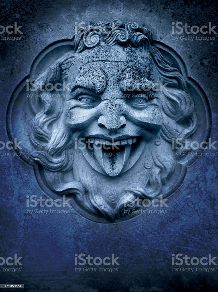Demon-like stone sculpture of face sticking out tongue stock photo